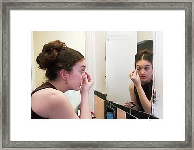 Teenage Girl Applying Make-up Framed Print by Jim West