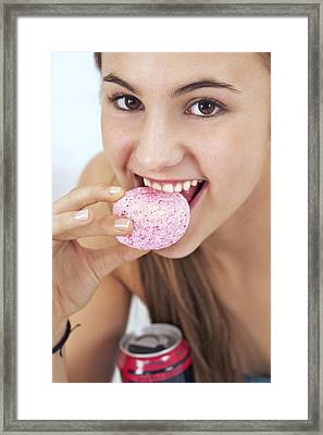 Teenage Girl Eating A Sugary Snack Framed Print by Science Photo Library