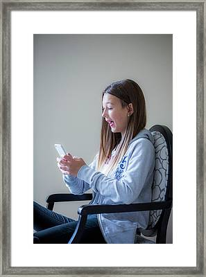 Teenage Girl Using A Smartphone Framed Print