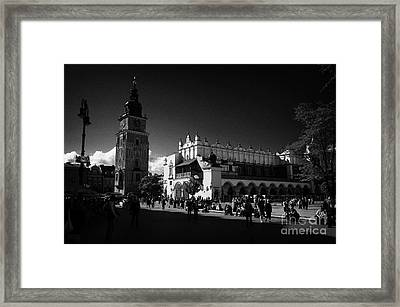 The 16th Century Cloth Hall Sukiennice Building And 13th Century  Gothic Town Hall Tower With Tourists In Rynek Glowny Town Square Krakow Framed Print by Joe Fox