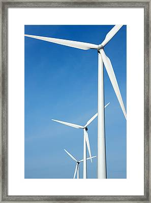 Three Mighty Windmills In A Row Against A Blue Sky. Framed Print