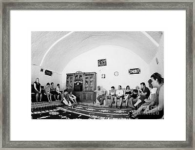 tour guide and coach load of british tourists the inside of main cave room of berber troglodyte underground dwelling at Matmata Tunisia Framed Print