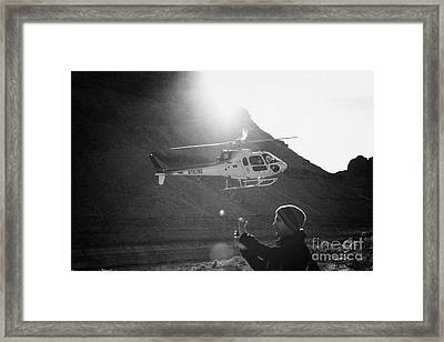 tourist taking photos with smart phone as papillon helicopter tours comes in to land in the Grand ca Framed Print by Joe Fox