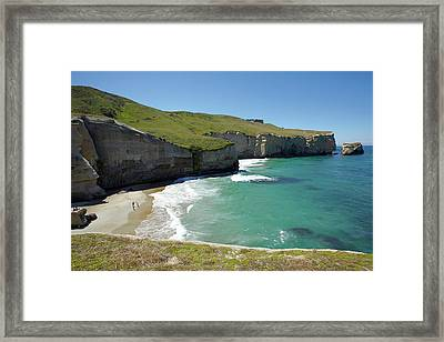 Tourists On Beach And Cliffs At Tunnel Framed Print by David Wall