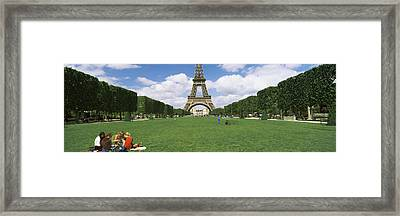 Tourists Sitting In A Park With A Tower Framed Print by Panoramic Images