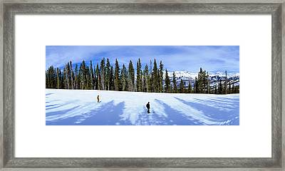 Tourists Skiing On Snow Covered Framed Print by Panoramic Images