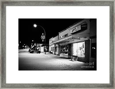 traditional window of fashion store at night in town of Biggar Saskatchewan Canada Framed Print by Joe Fox