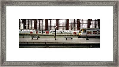 Trains At A Railroad Station Platform Framed Print