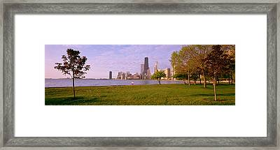 Trees In A Park With Lake And Buildings Framed Print by Panoramic Images