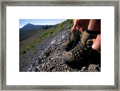 Two Hiking Boots Being Adjusted Framed Print