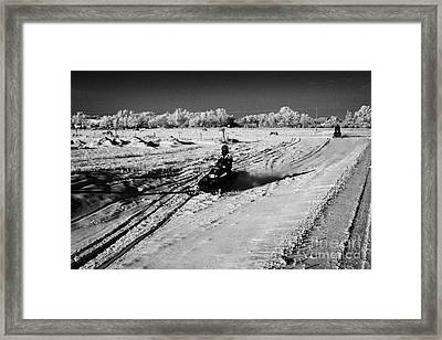 two men on snowmobiles crossing frozen fields in rural Forget Saskatchewan Canada Framed Print by Joe Fox