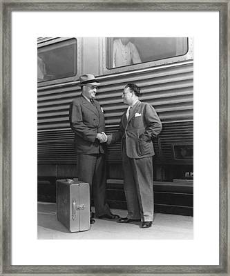 Two Men Shaking Hands At Train Framed Print by Underwood Archives
