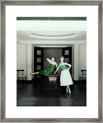 Two Models Posing By A Table Framed Print by John Rawlings