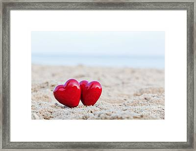Two Red Hearts On The Beach Symbolizing Love Framed Print by Michal Bednarek