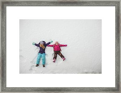 Two Sisters Playing, Making Snow Angels Framed Print by Hugh Whitaker