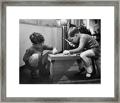 Two Young Boys Sitting By A Wooden Table Framed Print by Remie Lohse