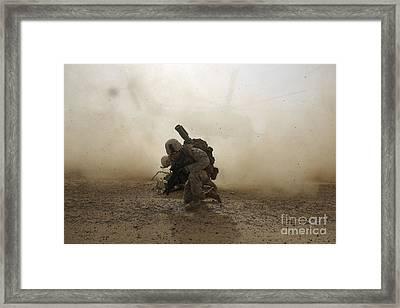 U.s. Marine Shields Himself From Dust Framed Print by Stocktrek Images