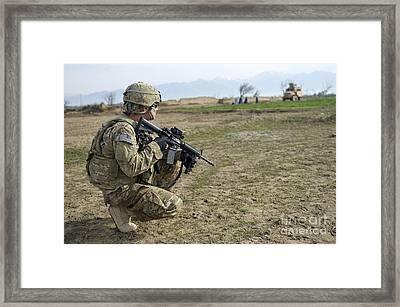 U.s. Soldier Patrols A Village Framed Print by Stocktrek Images