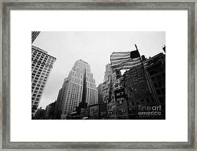 view of US flag flying on 34th street from 1 penn plaza new york city usa Framed Print