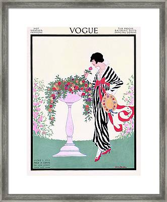 Vogue Cover Featuring A Woman Smelling A Rose Framed Print by Helen Dryden