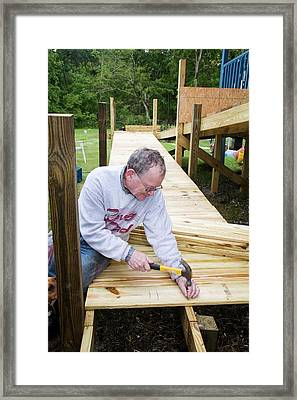 Volunteer Building A Wheelchair Ramp Framed Print by Jim West