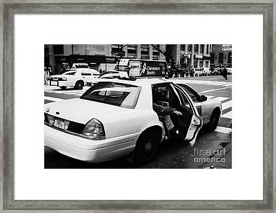 white caucasian passenger closes rear door of yellow cab on taxi rank at crosswalk on 7th Avenue Framed Print
