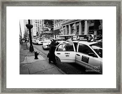 white middle aged passengers exit from yellow cab rear door at taxi rank on 7th Avenue Framed Print
