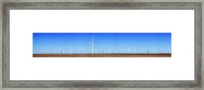 Wind Turbines In A Field Against Blue Framed Print by Panoramic Images