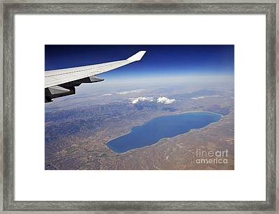 Wing Of Flying Airplane Over Lake And Mountains Framed Print by Sami Sarkis
