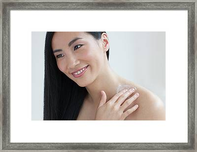 Woman Applying Body Cream Framed Print