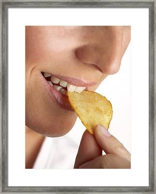 Woman Eating A Crisp Framed Print