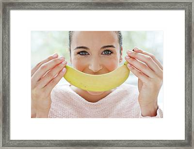 Woman Holding A Banana In Front Of Face Framed Print by Ian Hooton