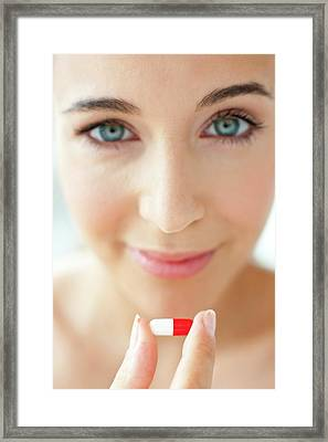 Woman Holding A Red And White Capsule Framed Print