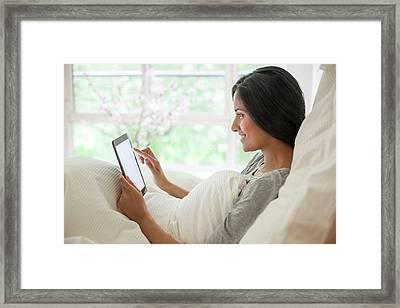 Woman In Bed Using Digital Tablet Framed Print
