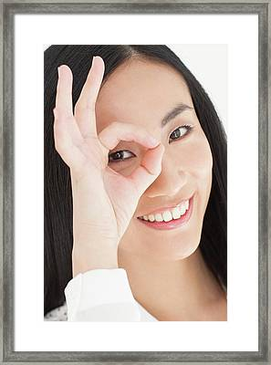 Woman Looking Through Fingers Framed Print by Ian Hooton