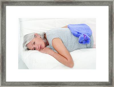 Woman Lying Down With Hot Water Bottle Framed Print by Lea Paterson