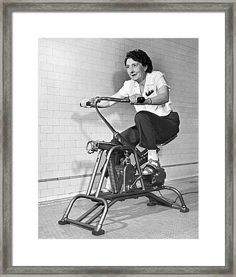Woman On Exercycle Framed Print