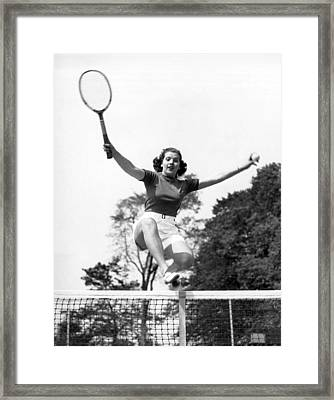Woman Player Leaping Over Net Framed Print by Underwood Archives