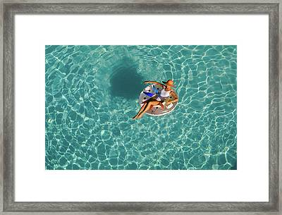 Woman Sitting On Float In Swimming Pool Framed Print