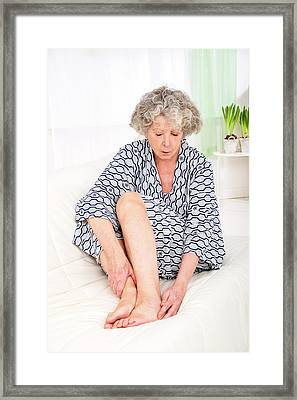 Woman Touching Her Ankle Framed Print by Lea Paterson