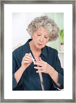 Woman Using Finger Prick Test Framed Print by Lea Paterson