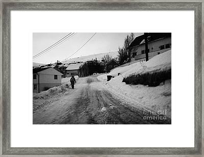 woman walking down steep ice covered street in Honningsvag finnmark norway europe Framed Print by Joe Fox