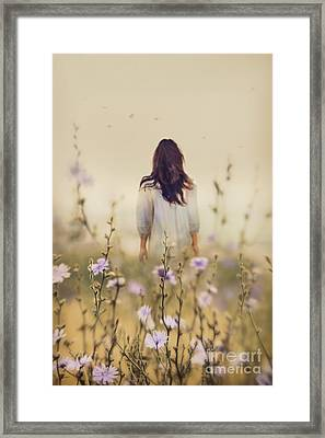 Woman Walking In Field Of Blue Flowers Framed Print by Sandra Cunningham