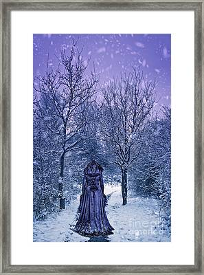 Woman Walking In Snow Framed Print by Amanda Elwell
