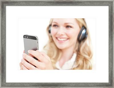 Woman Wearing Headphones Holding Smartpho Framed Print by Ian Hooton