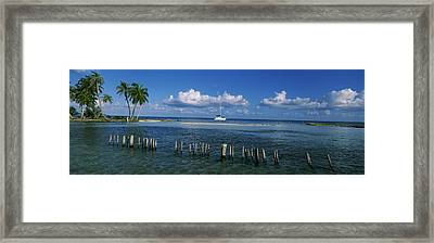Wooden Posts In The Sea With A Boat Framed Print by Panoramic Images