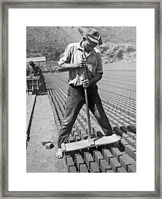 Worker Stamping Out Bricks Framed Print