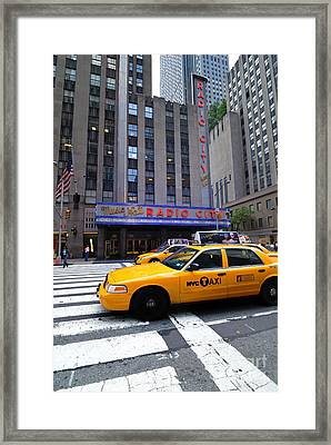 Yellow Cabs Pass In Front Of Radio City Music Hall Framed Print by Amy Cicconi