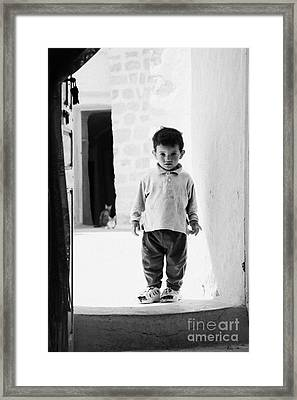 young berber troglodyte boy standing in the entrance doorway to cave in underground dwelling at Matmata Tunisia Framed Print