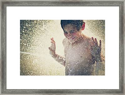 Young Boy In Splashing Water Backlit By Framed Print by Fran Polito